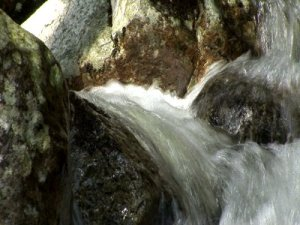 stock-footage-zoom-out-of-water-rounding-corner-spilling-over-rock-and-cascading-into-natural-pool
